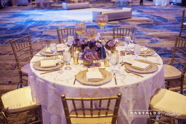 wedding reception table in gold and purple