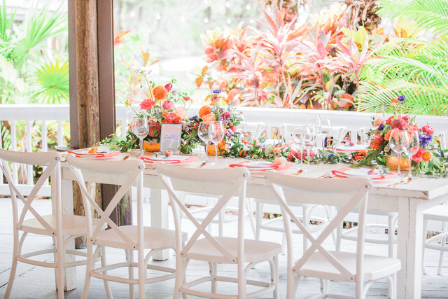white farmhouse reception table with colorful floral runner