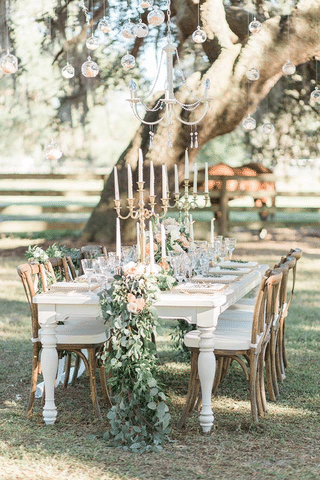 outdoor wedding reception table with chandeliers