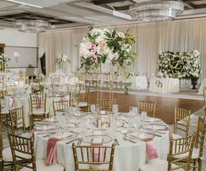 A Chair Affair - reception hall with gold chairs and stunning floral centerpieces