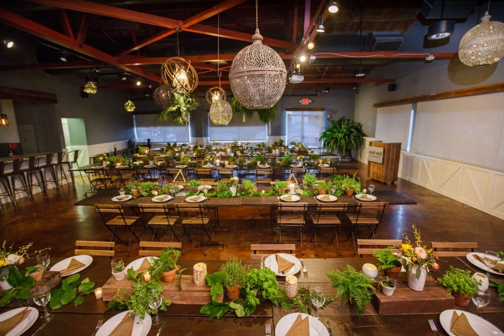 Audubon Park Exchange Ballroom - reception hall with wooden folding chairs and greenery table centerpieces