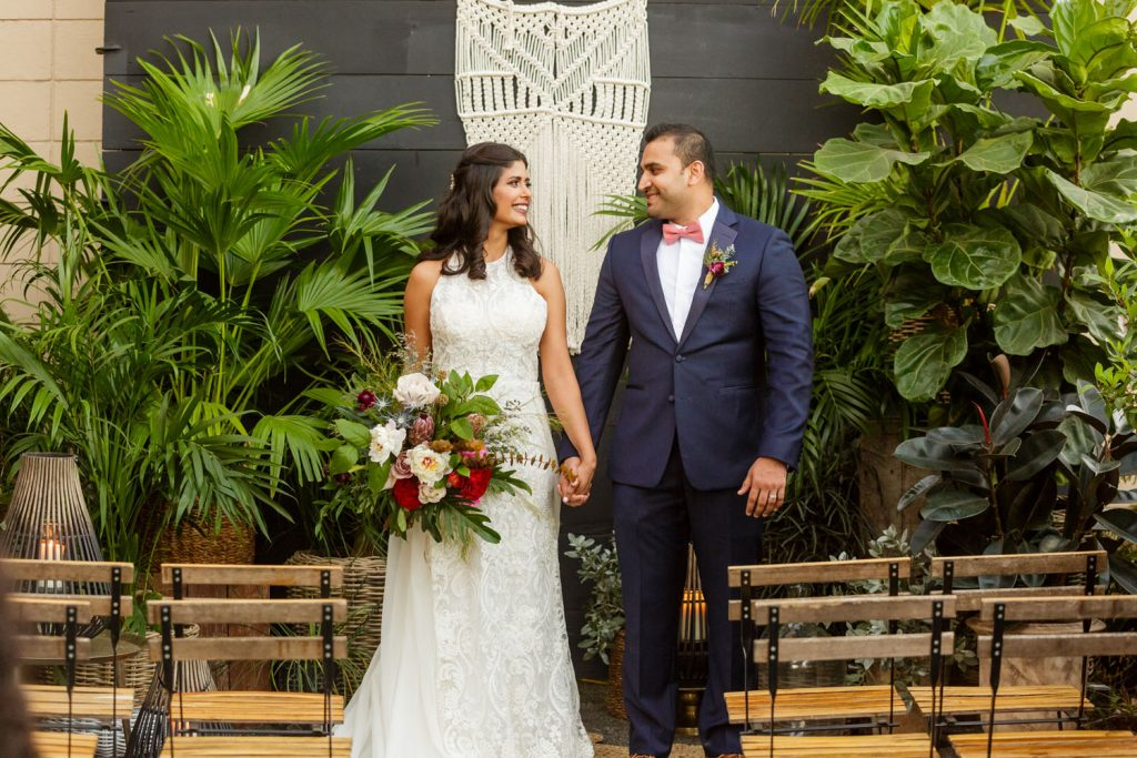 Audubon Park Exchange Ballroom - newlyweds posing by macrame wall hanging