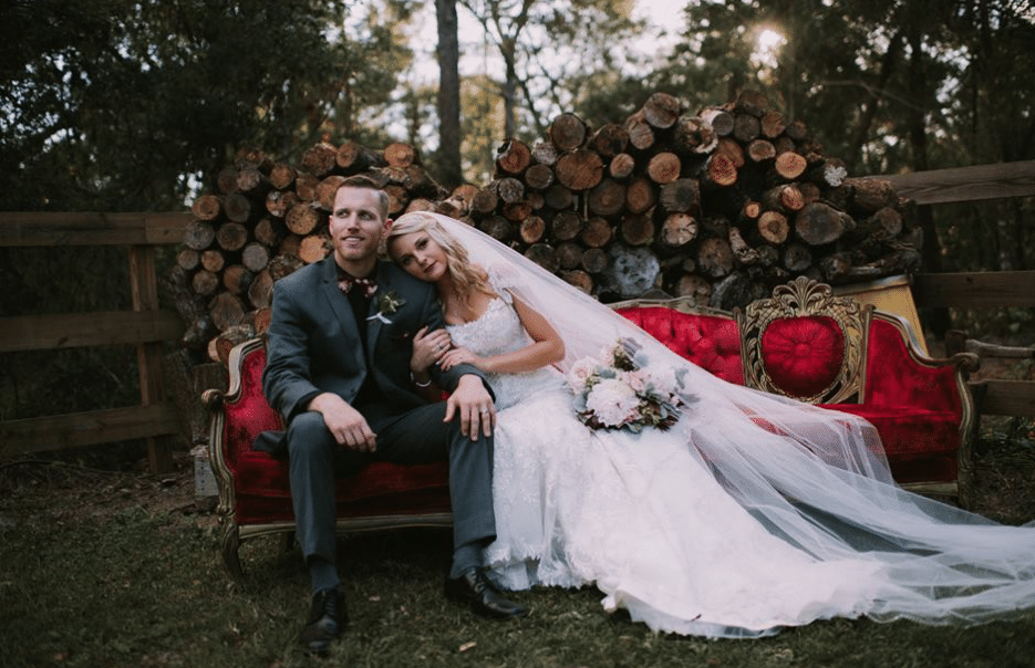 Bridle Oaks Barn - Bride and groom on velvet couch outside