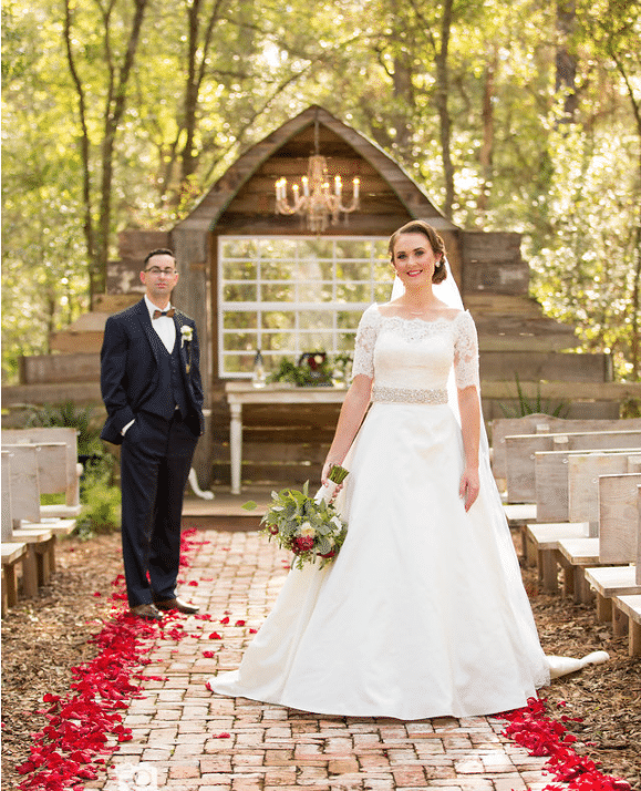 Bridle Oaks Barn - ceremony space with rustic wooden backdrop