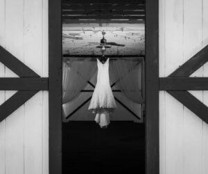 Bridlewood-Ranch-Wedding dress hanging in barn between barn doors