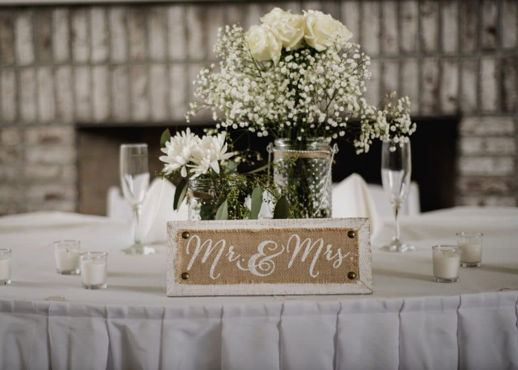 Celebration-Golf-Club-Mr. and Mrs. wooden plaque on table at reception with white roses and babybreath floral centerpiece