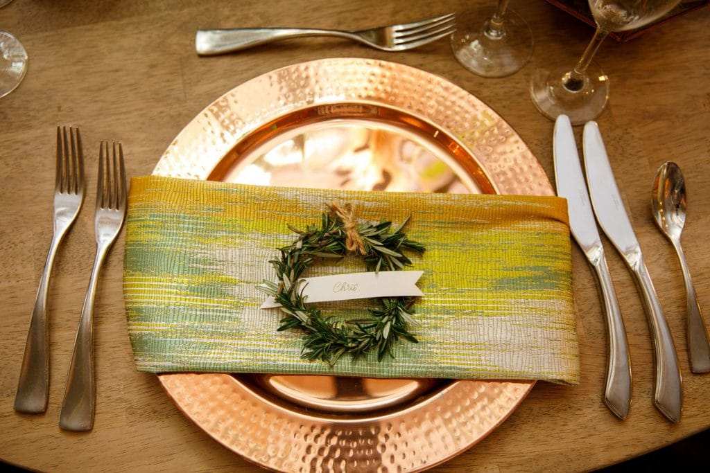 Citrus Club - table setting with gold charger, green and gold napkin, and rosemary wreath