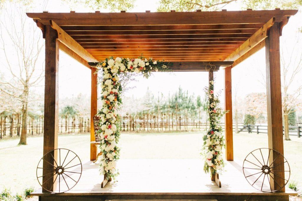 Club Lake Plantation - gorgeous outdoor pergola with wagon wheels and romantic flowers