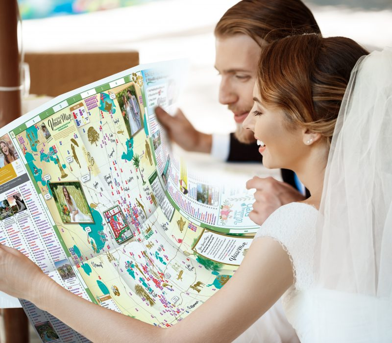 Young beautiful newlyweds smiling, choosing honeymoon trip, looking at map, sitting in cafe.