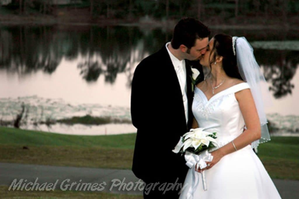 Debary-Golf-Country-Club-Bride and Groom kissing by lake at dusk