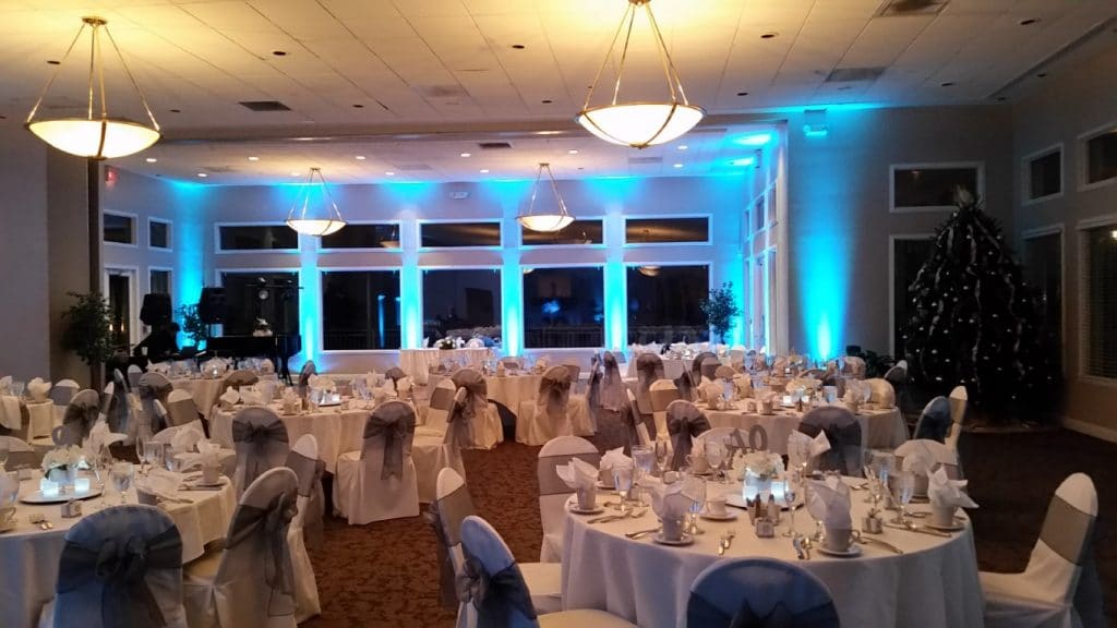 Debary-Golf-Country-Club-Large reception area set up with table and chairs and blue uplighting