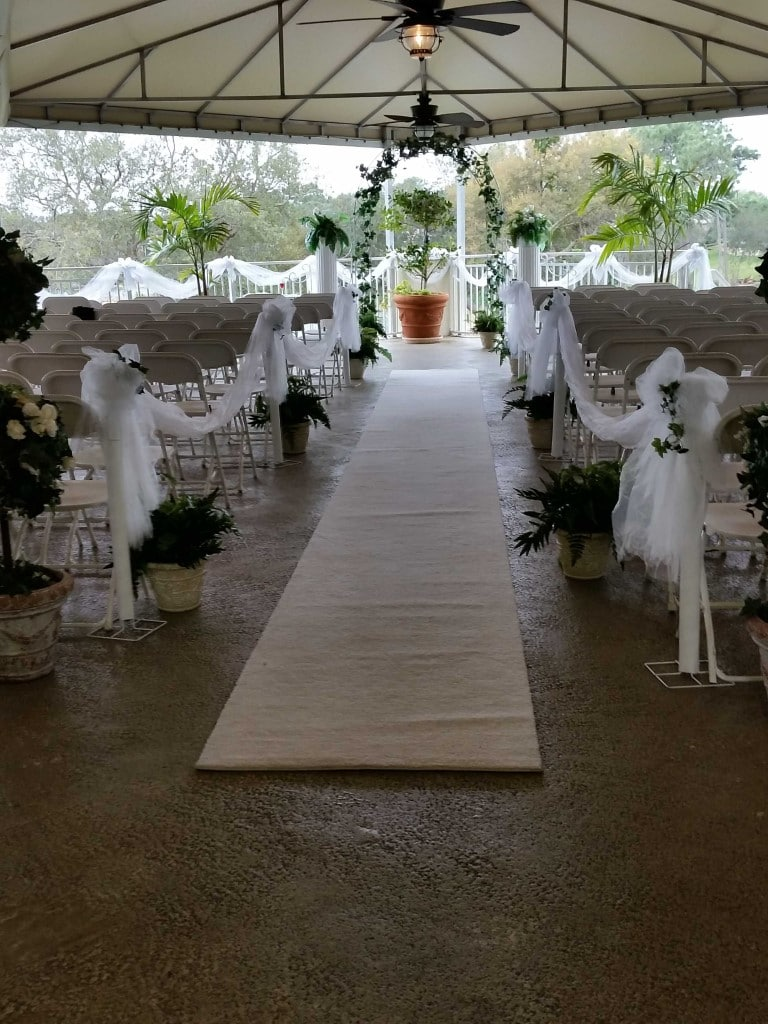 Debary-Golf-Country-Club-White carpet aisle lined with flowers in covered outdoor area