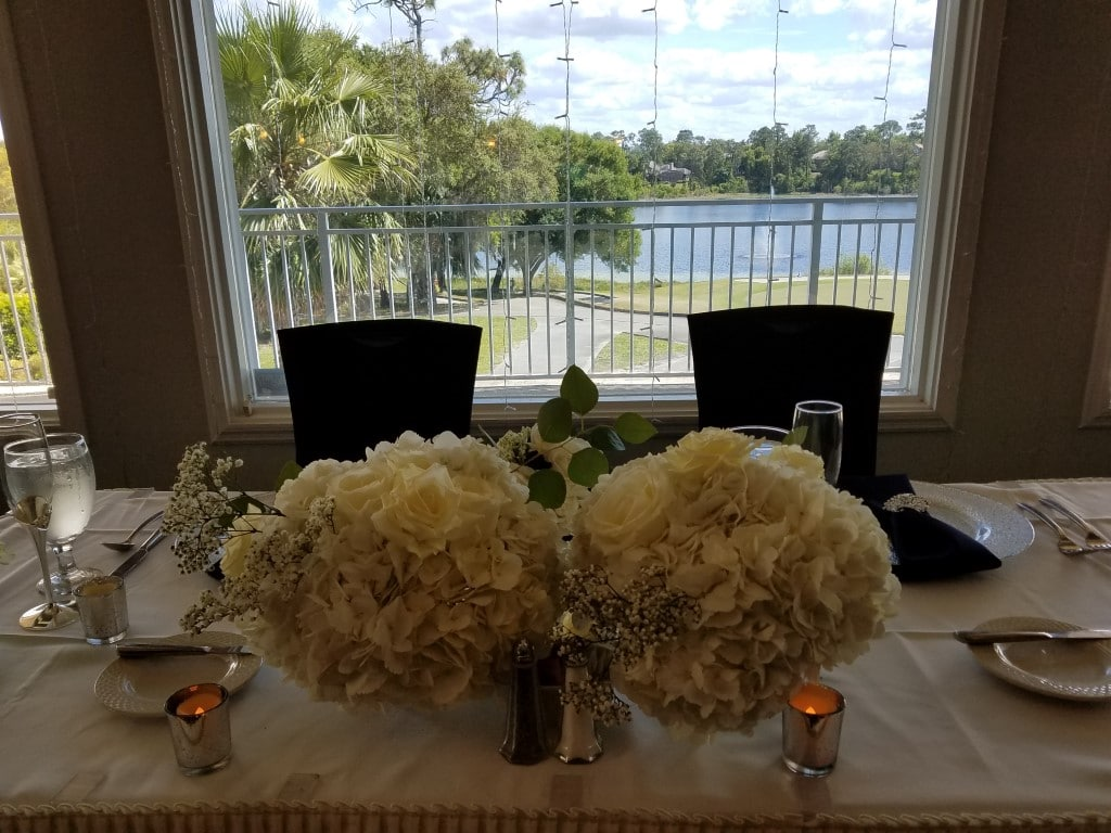 Debary-Golf-Country-Club-Couple table with dual floral centierpiece with large picture window view