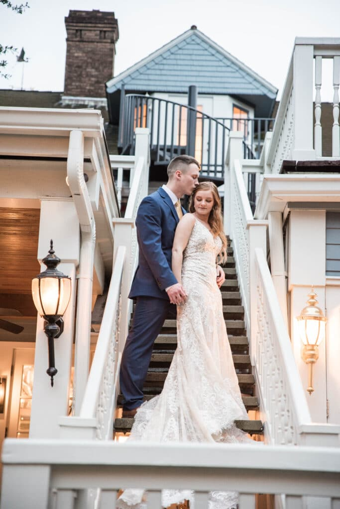 Dr Phillips House Downtown Orlando Wedding Venue bride and groom standing on outdoor steps with groom kissing top of brides head