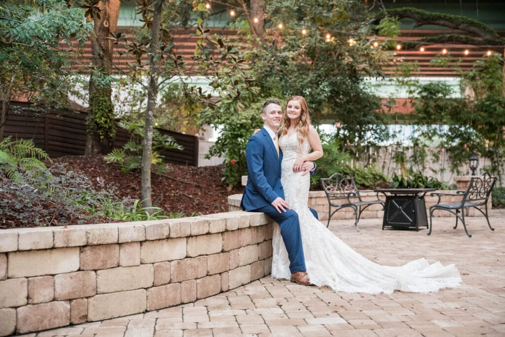 Dr Phillips House Downtown Orlando Wedding Venue groom sitting in courtyard with arm around brides waist