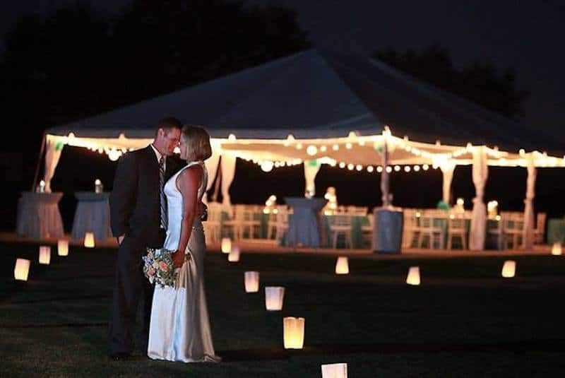 Falcon's Fire bride and groom kissing outside at night with lit tent for wedding reception in background