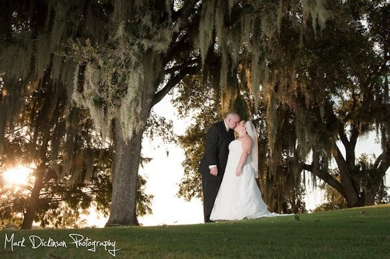 Falcon's Fire bride and groom kissing outside under moss tree