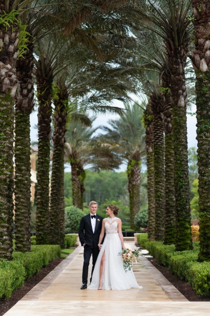 Four-Seasons-at-Walt-Disney-World-Bride and Groom walking on sidewalk surrounded by palm trees