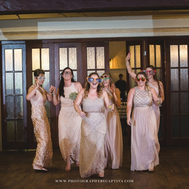 Historic-Dubsdread-Ballroom-Bridesmaid entering reception wearing photobooth props