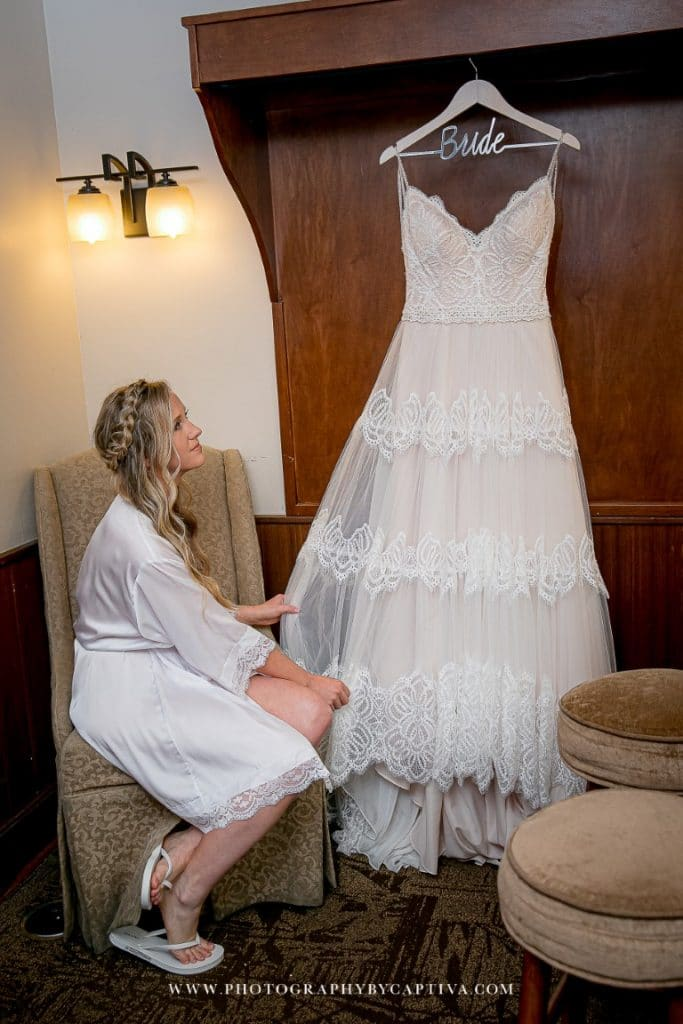 Historic-Dubsdread-Ballroom-Bride gazing happily at her hanging wedding dress before the ceremony