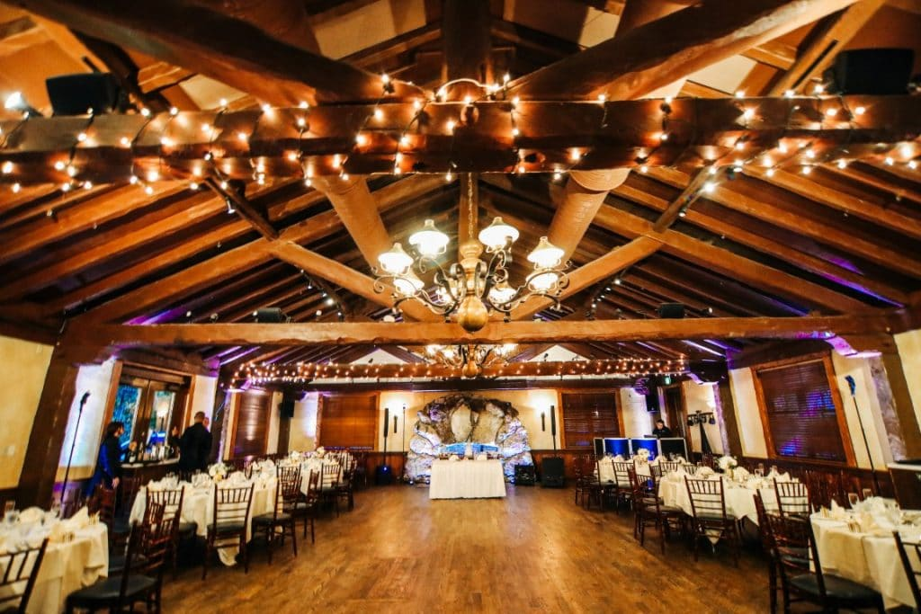 Historic-Dubsdread-Ballroom-Brightly lit reception ballroom with several table settings and Bride & Groom table.