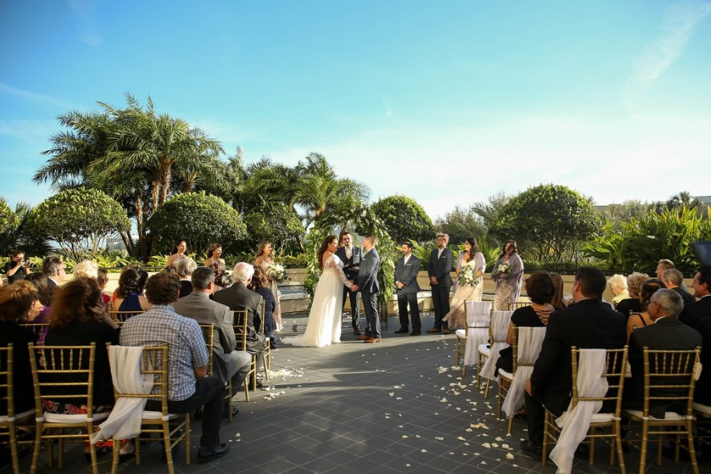 Hyatt-Regency-Orl-Wedding Ceremony outside by garden under blue sky
