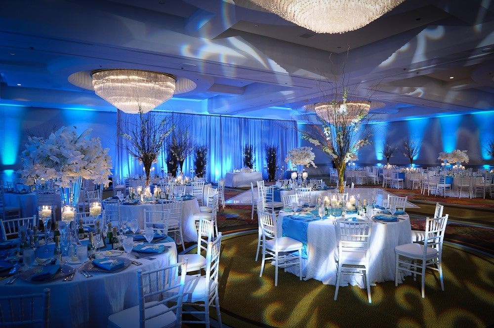Hyatt-Regency-Orl-Ballroom decorated in silver and blue hues with subtle lighting and floral centerpieces