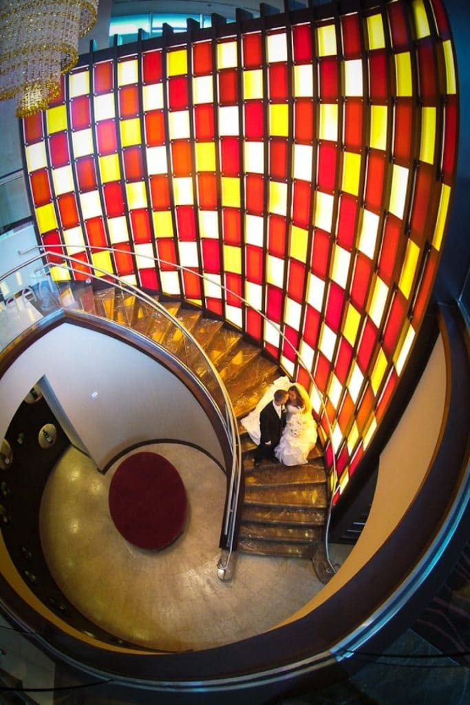 Hyatt-Regency-Orl-Birds Eye view of circular staircase next to yellow and red checkered glass wall