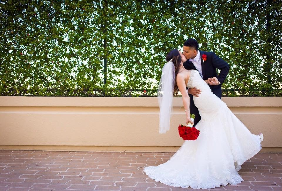 Hyatt-Regency-Orl-Groom dipping Bride with a kiss by greenery wall