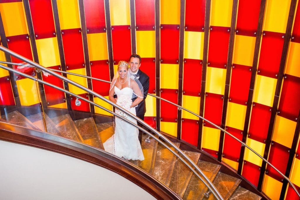 Hyatt-Regency-Orl-Bride and Groom staning on circular stairwell in front of yellow and red checkered glass wall
