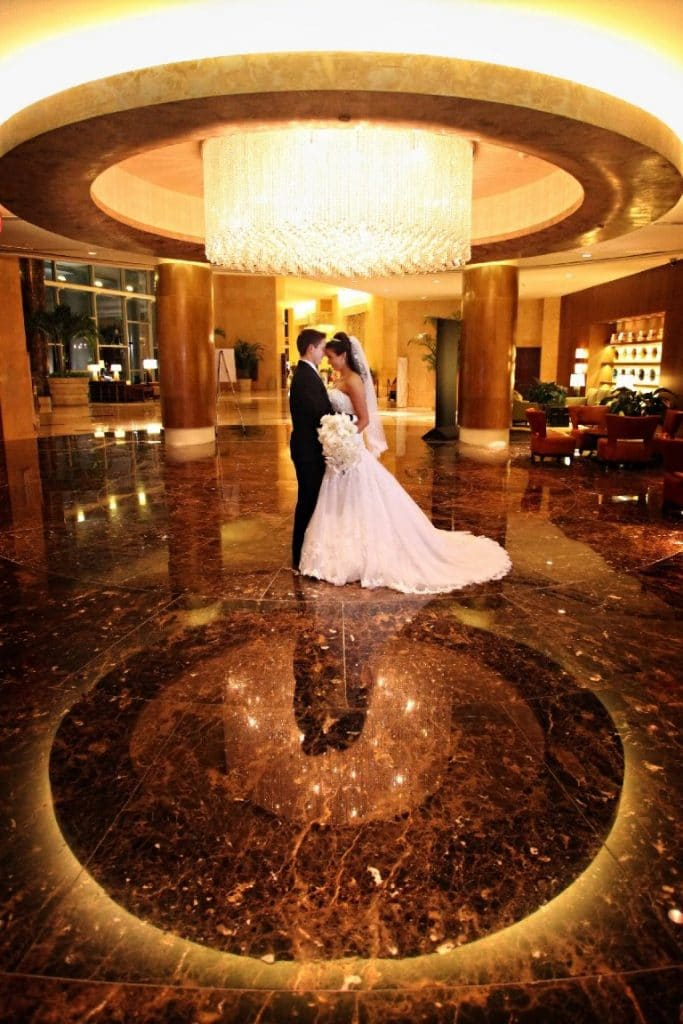 Hyatt-Regency-Orl-Bride and Groom embracing in the middle of a beautiful entry way