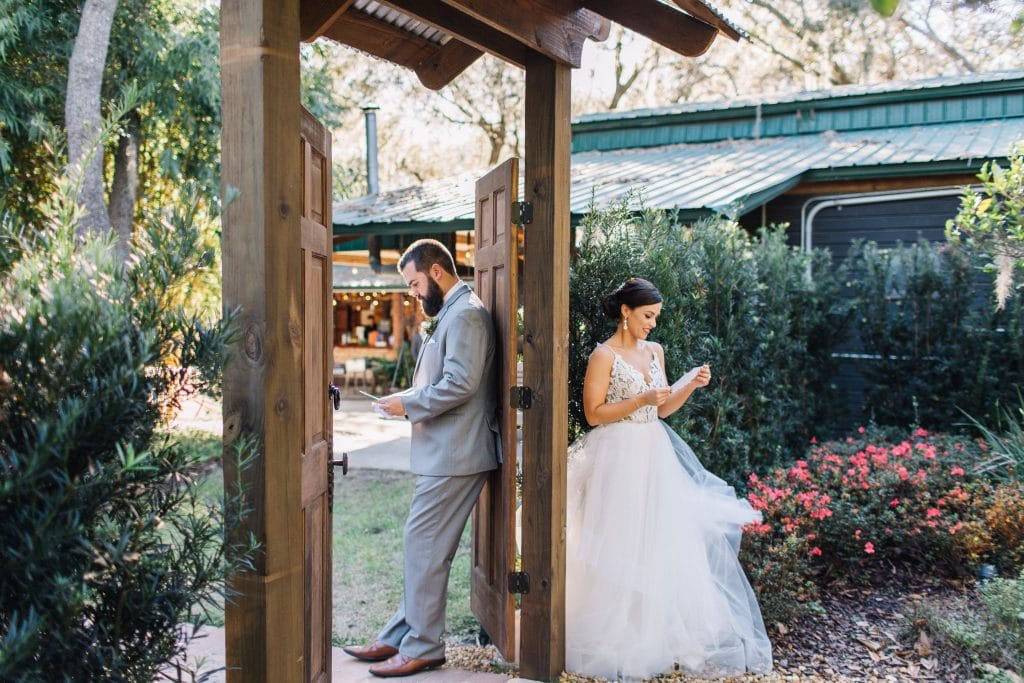 bride and groom reading letters on opposite sides of door
