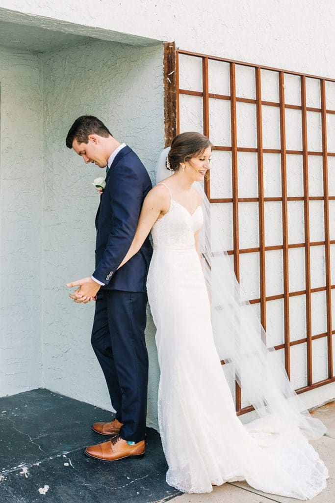 bride and groom holding hands with backs together