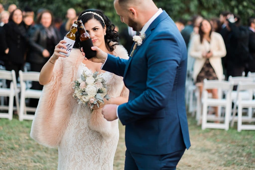 bride and groom toasting each other with beer bottles