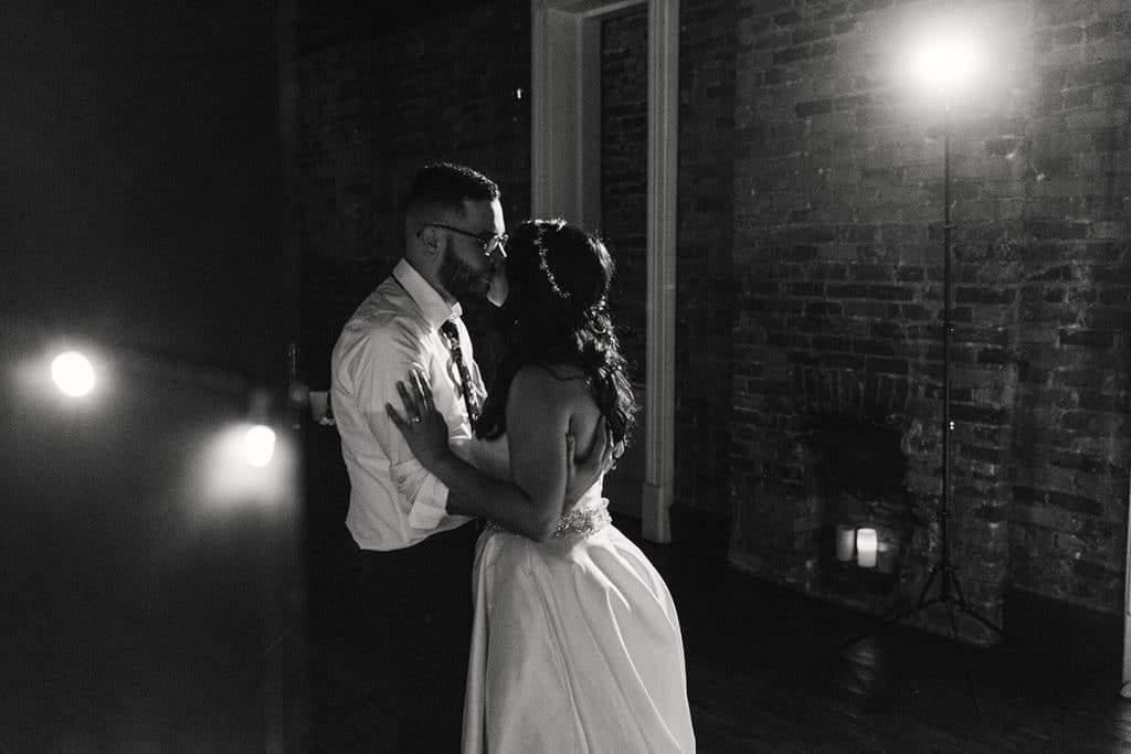 black and white photo of bride and groom dancing alone