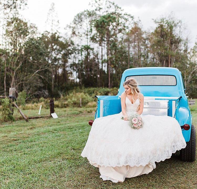 bride on antique blue truck at mystical winds