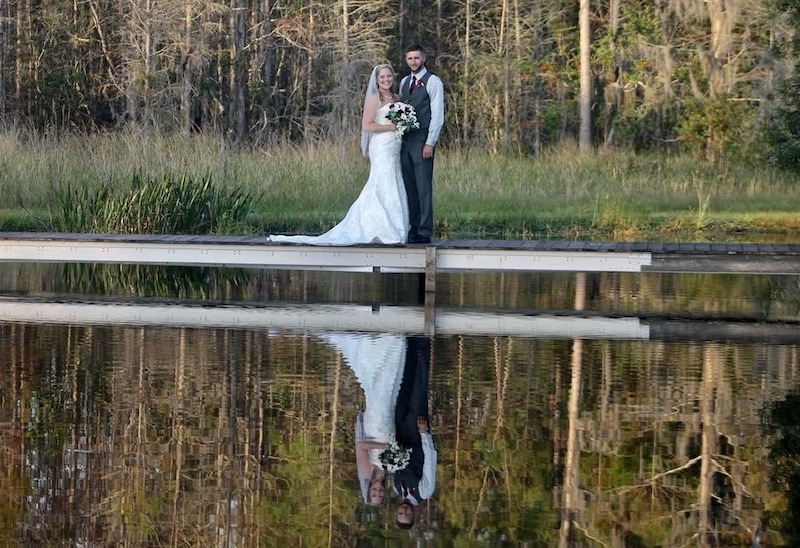 Mystical Winds bride and groom standing on dock overlooking lake