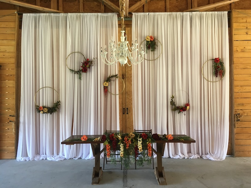Mystical Winds wedding reception decorations with curtains and chandelier