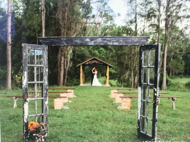 Mystical Winds bride and groom standing under arch for outdoor wedding reception