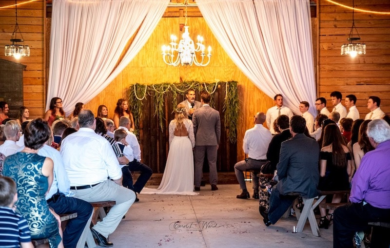 Mystical Winds bride and groom getting married inside under chandelier with guests watching