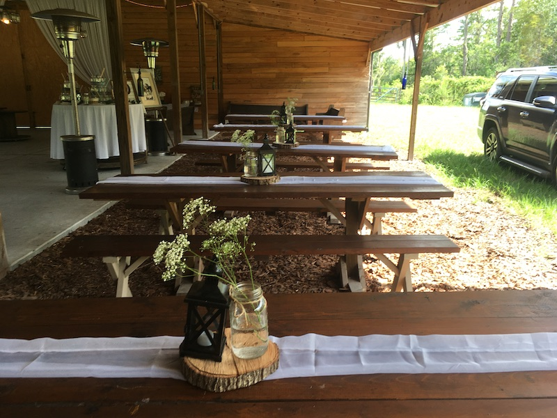 Mystical Winds outdoor tables under overhang with centerpieces