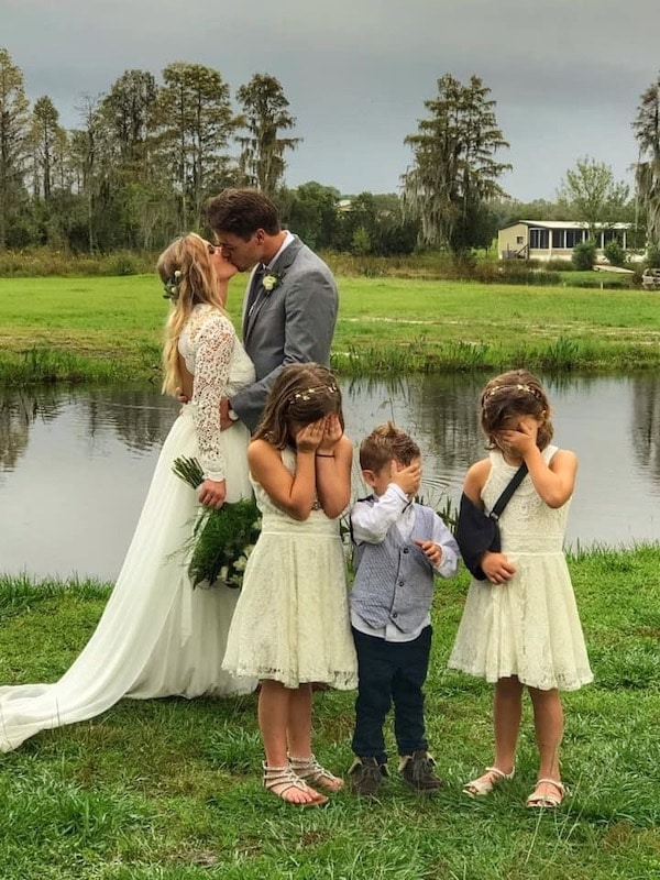 Mystical Winds bride and groom kissing outside with kids covering their eyes