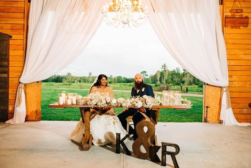 Mystical Winds sweetheart table at wedding reception with view of fields behind them