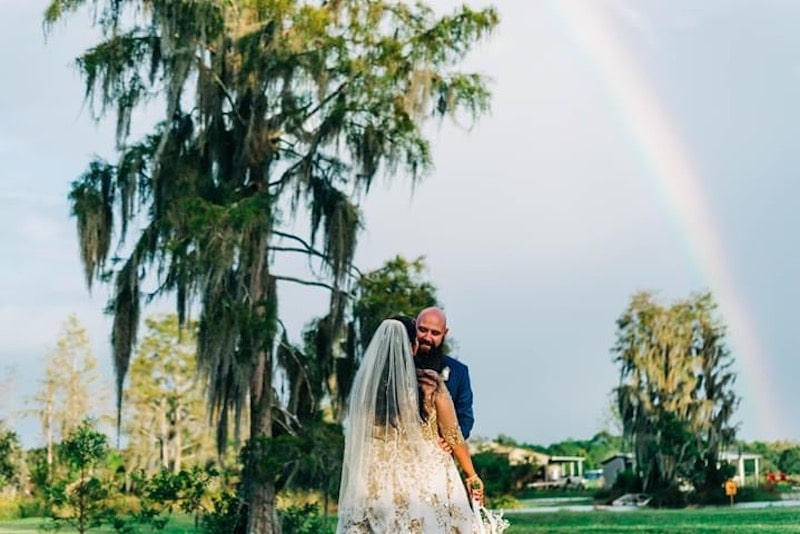 Mystical Winds bride and groom outside underneath a moss covered tree and a rainbow