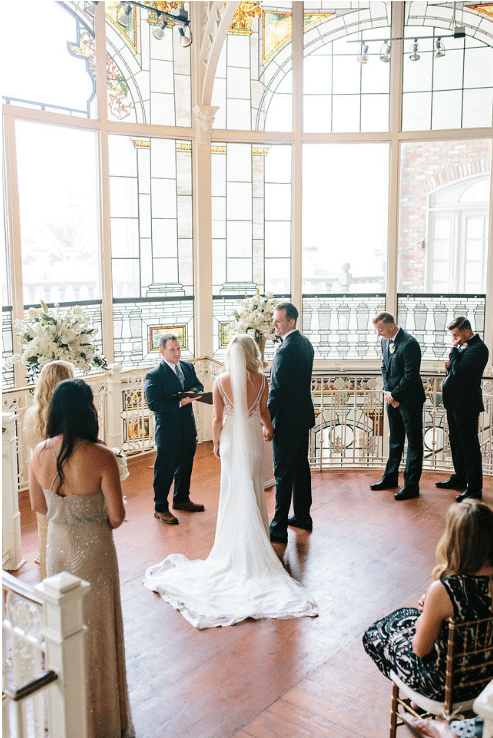 Orchid-Garden-at-Church-Street-Couple holding ceremony in front of large windows with natural light and bridal party standing around them