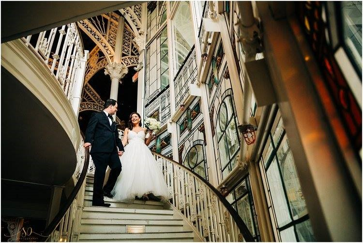 Orchid-Garden-at-Church-Street-Bride and Groom holding hands walking down staircase