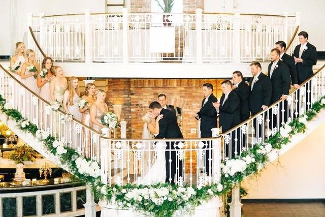 Orchid-Garden-at-Church-Street-Bridal party standing on outdoor staircase as bride and groom kiss