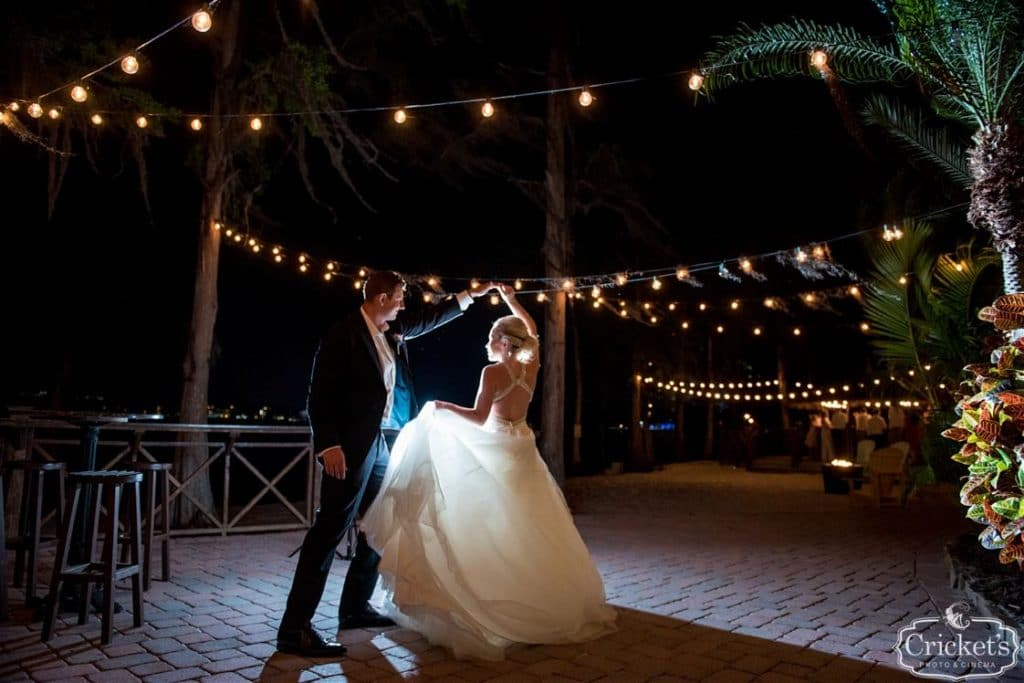 Paradise Cove - groom spinning bride under market lights in a tropical setting