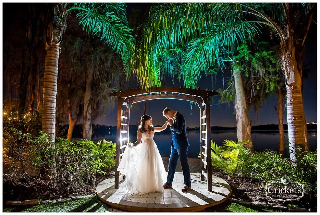 Paradise Cove - groom kissing bride's hand under tropical pergola