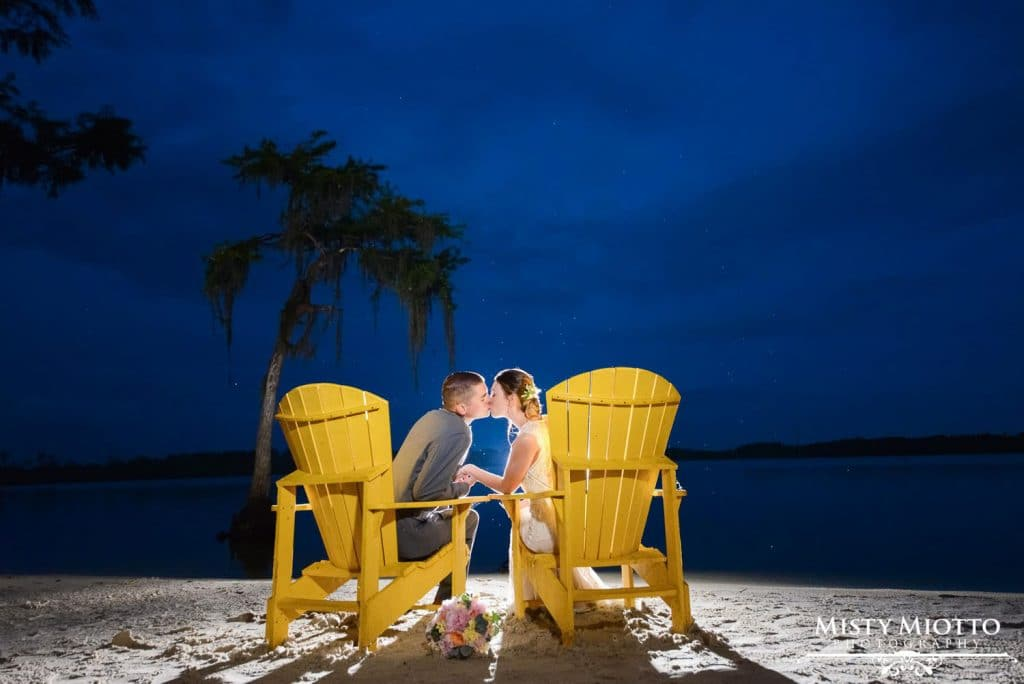 Paradise Cove - bride and groom in Adirondack chairs on sandy lakeshore